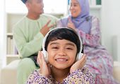foto of malay  - Muslim girl listening to song at home - JPG