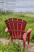 foto of bull rushes  - Red plastic Adirondack chairs placed for a view of the river - JPG
