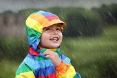 stock photo of innocence  - Little boy enjoying the rain dressed in a rainbow colored raincoat - JPG