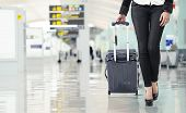 image of pull up  - Young woman pulling luggage at the airport close up sexy legs - JPG