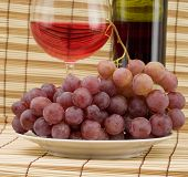 stock photo of loamy  - Glass bottle goblet and grape on wooden mat