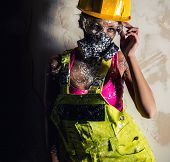 pic of respiration  - Female construction worker wearing coverall hardhat and respirator posing over obsolete wall - JPG