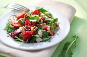 stock photo of vinegar  - Salad with arugula strawberries goat cheese and walnuts dressed with balsamic vinegar and olive oil - JPG