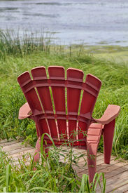 stock photo of bull rushes  - Red plastic Adirondack chairs placed for a view of the river - JPG