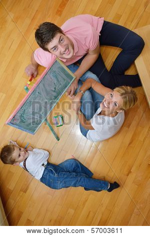 happy young family teach leassons and prepare their son for school while draw on board at home