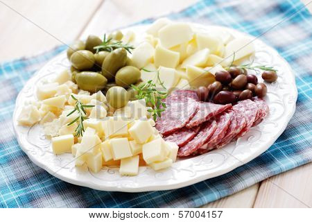 cheese and olives on a plate as a snack - food and drink