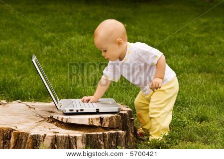 Little Child Playing With Notebook On The Grass