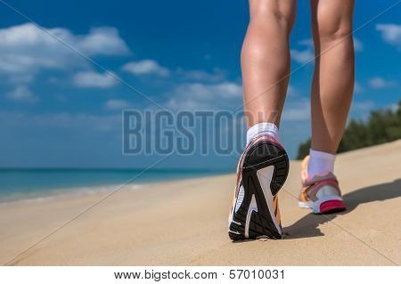 Close up of feet of a runner running in the beach training for marathon and fitness healthy lifestyl