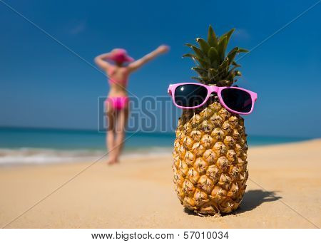 Cheerful pineapple glasses and a woman in a bikini sunbathing on the beach on sea background. Ideali