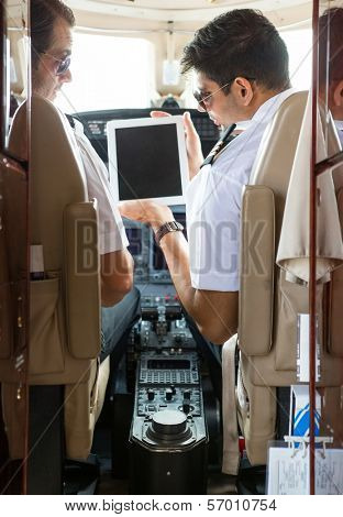 Pilot showing digital tablet to copilot in cockpit of private plane