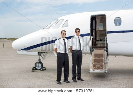Full length of confident pilots standing in front of private jet with open door