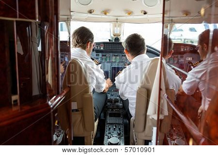 Rear view of pilot and copilot operating controls of private jet
