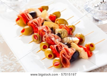 Antipasti skewers with olives,red pepper,artichoke hearts and salami