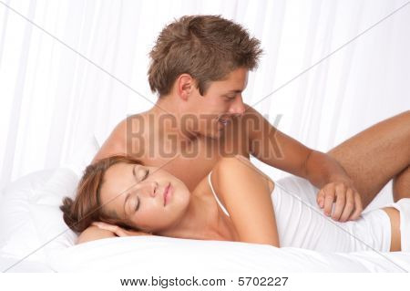 Young Man And Woman Lying Down In White Bed
