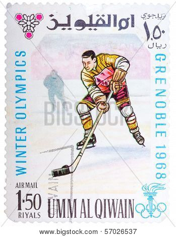 Stamp Printed By Umm Al-quwain, Shows Hockey Player Bats The Puck
