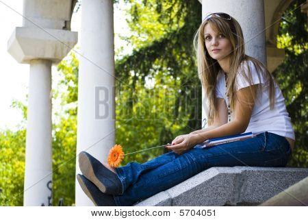 Hermosa joven con libros y flores