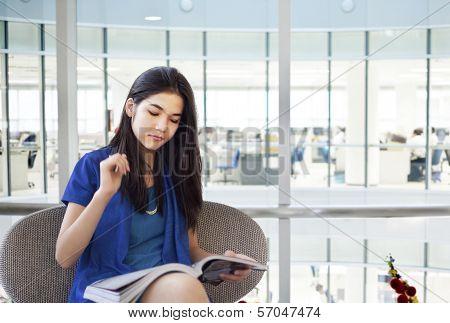 Beautiful Teen Girl Reading Magazine In Office