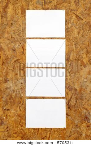 Four Laminated Pieces Of White Paper Stapled On An Old Recycled Wood Board.