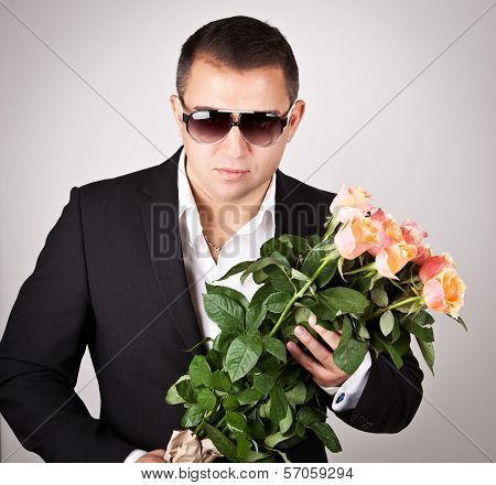 Portrait A Young Man In Suit With Bouquet Of Roses