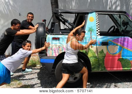 Teens and child pushing a car