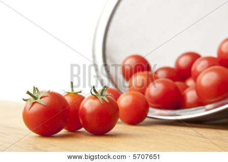 Fresh Tomatoes In Colander On Cutting Board