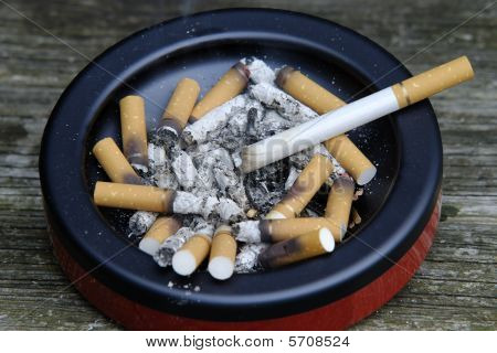 Smoking Cigarette With Butts And Ends In Ashtray