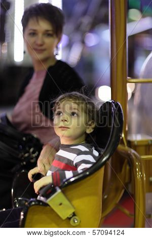 Mother Woth Her Son On Carousel