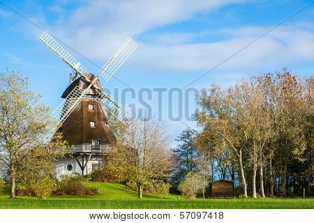 Traditional Wooden Windmill In A Lush Garden