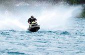 pic of jet-ski  - Young man riding jet ski with much splashes - JPG