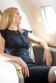 picture of diva  - Attractive rich woman looking through window in private jet - JPG