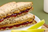Healthy and delicious childs lunch of peanut butter and jelly sandwich with green apples and milk