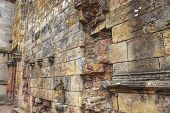stock photo of rosslyn  - Weathered and ruined outdoor wall of 15th century Rosslyn Chapel in Scotland before the restoration - JPG