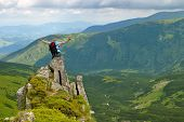 foto of splayed  - Woman in montains on rock with back pack with his arms splayed and say - JPG