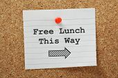 stock photo of jargon  - The phrase Free Lunch This Way with a direction arrow typed on a piece of paper and pinned to a cork notice board - JPG