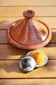 image of tagine  - Three containers with spices like curry on a wood table.