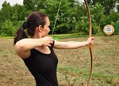 stock photo of longbow  - Young women training with the bow and green arrow - JPG