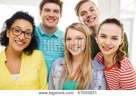 education and happiness concept - group of young smiling people at home or school