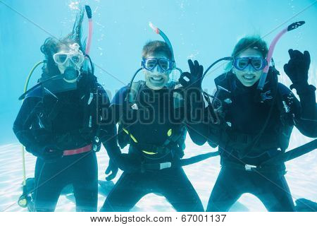 Friends on scuba training submerged in swimming pool making ok sign on their holidays