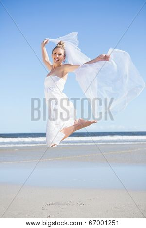 Pretty blonde in white dress holding up shawl on the beach on a bright day