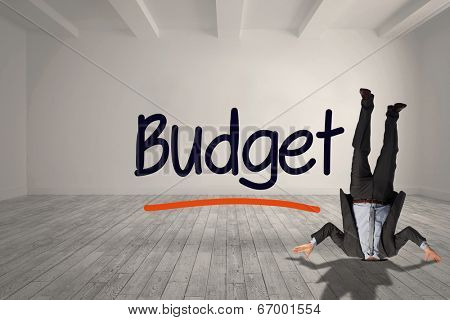 Businessman burying his head against budget written in bright room