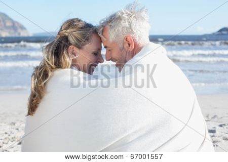 Couple sitting on the beach under blanket smiling at each other on a sunny day