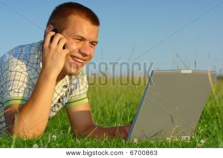 Happy Student Working With Laptop On Green Meadow