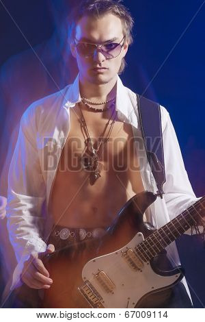 Male Guitarist Posing With Guitar. Shot With Strobes And Halogen Light On Slow Shutter Speed. Mixtur