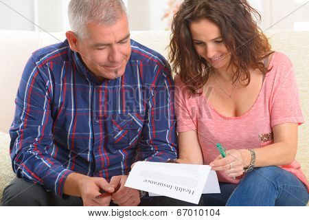 Mature ouple signing health insurance contract at home