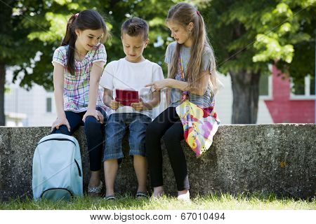 Children playing video games outdoors