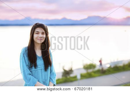 Beautiful Young Teen Girl Enjoying Outdoors By Lake At Sunset