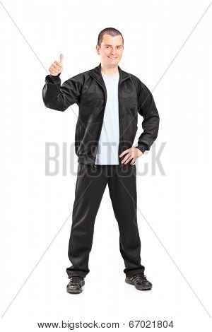 Full length portrait of a young man in black tracksuit giving a thumb up isolated on white background