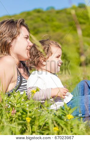 young happy mother playing with her child girl outdoors