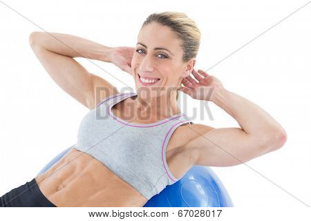 Fit woman doing sit ups on blue exercise ball smiling at camera on white background