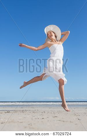 Pretty blonde in white dress leaping on the beach on a bright day